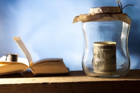 Jar with money, college graduation cap and open book.  Stock Photo - 22582550