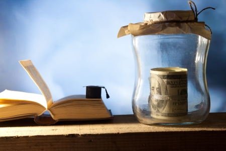 Jar with money, college graduation cap and open book. Stock Photo - 22582551