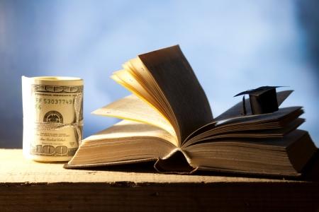 examiert: Price Leaving Certificate or training. Mini college graduation cap, cash and open book. Stock Photo