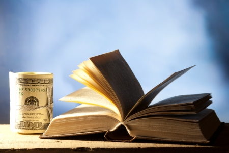 Open book with dollar banknotes (Roll of One Hundred Dollar) - tuition or education financing concept.