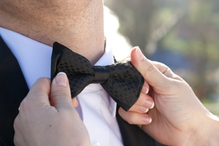 Women's hands touches bow-tie on a suit. photo