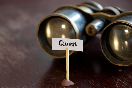 quest: Quest concept, old binoculars and an inscription quest Stock Photo