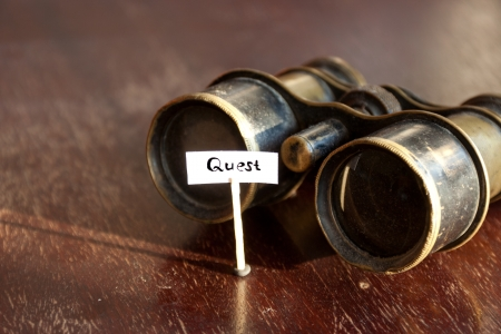 Quest concept, old binoculars and an inscription quest Stock Photo
