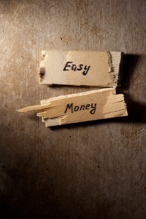 scheming: easy money concept, wooden surface Stock Photo