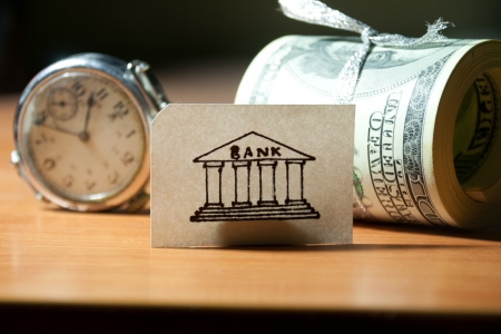 Time, money, bank concept. watches, bank, roll of banknotes. photo