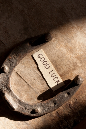 grungey: good luck inscription and  horseshoe over wooden background Stock Photo