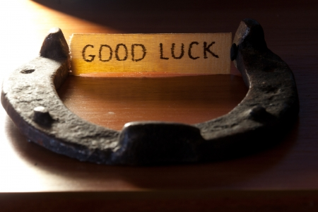 goodluck: good luck inscription and  horseshoe over wooden background Stock Photo