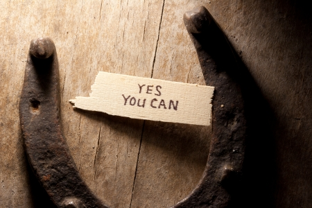 yes you can  inscription and  horseshoe over wooden background Stock Photo