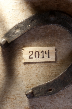 tags with 2014 on a wooden surface and horseshoe
