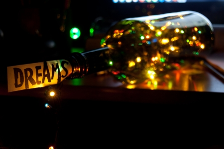 Dreams concept. The word dream, bottle and multicolored lights Stock Photo