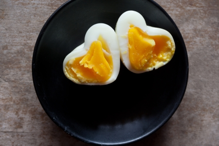 Heart Shaped Eggs on a wooden table. photo