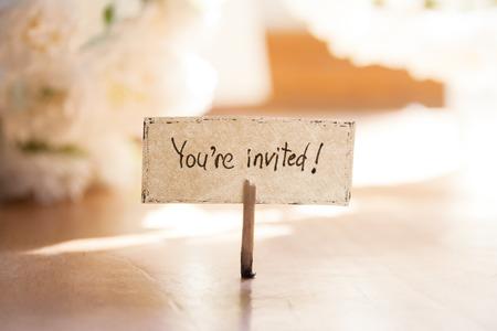 U wordt uitgenodigd hand belettering, witte bloemen op de achtergrond, uitnodiging.
