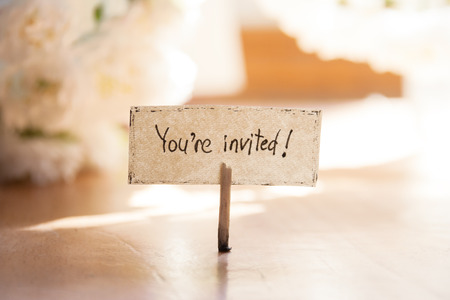 Youre Invited hand lettering, white flowers on background, invitation. Stock Photo