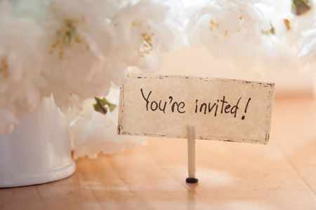 invited: Youre Invited hand lettering, white flowers on background, wedding invitation.