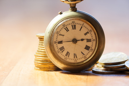Time is money concept. Coins and an old pocket-watch. photo