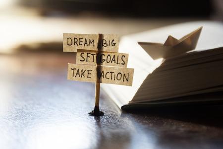 dream: Dream Big, stanovit cíle, jednat, koncept, značky na stole.