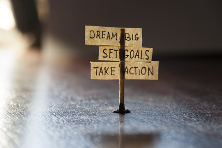 business goal: Dream Big, Set Goals, Take Action, concept, tags on the table. Stock Photo