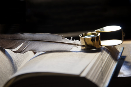 Close-up of open book, quill pen  and magnifying glass photo