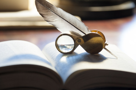 Close-up of open book, quill pen  and magnifying glass