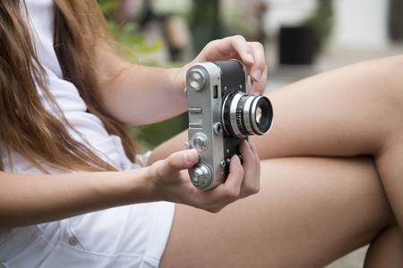 girl holding vintage camera outdoors photo