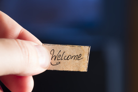 welcome hand lettering, hand holding a tag welcome