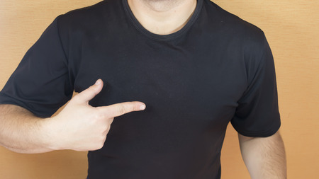 Man with muscular torso pointing his finger on a blank tshirt Stock Photo
