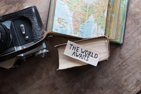 """tekst """"The World Awaits"""" en boek, reis, toerisme begrip"""