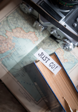 Text Just go book and map. Travel and tourism concept. Vintage photo.