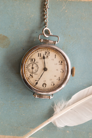 Retro background, old watches on a blue background and feather,  vintage.The Victorian era. Writer, literature, old school, polite learning concept. Stock Photo