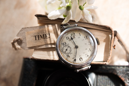 Time concept, retro pocket watch on  a book and label time.
