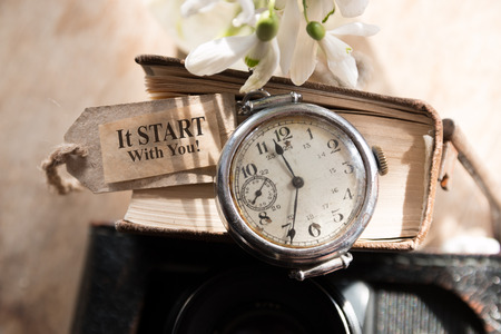 It Starts With You! Watches, flowers, books and inscription.