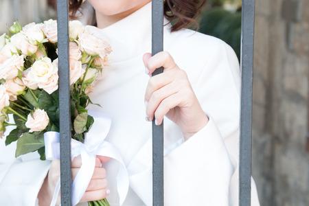 behind bars: bride with flowers behind bars
