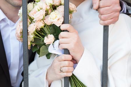 behind bars: bride with flowers and groom behind bars