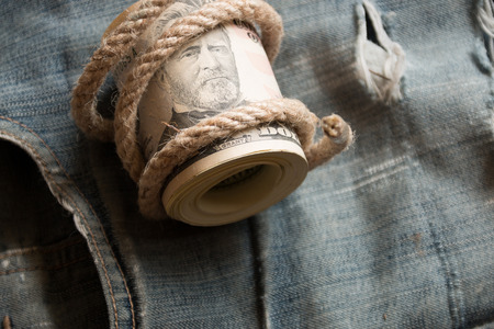 fifties: Dollars  lying on old jeans. A roll of fifties.