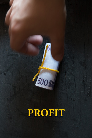 Profit - Business Concept. Roll of money on a dark table hand and an inscription. photo
