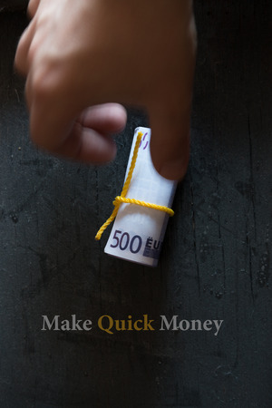 money roll: Make Quick Money. Roll of money on a dark table hand and an inscription.