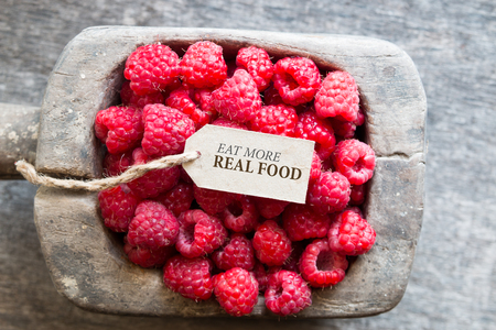 Eet meer echt voedsel, frambozen en een label met het opschrift Stockfoto