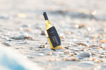 august: Summer party concept. Inscription on the bottle, the bottle on the beach. Stock Photo