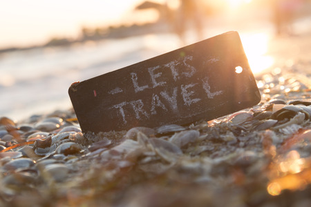 Lets go travel, adventure motivation concept. Sign with the text Let's Travel on the beach, sunset.