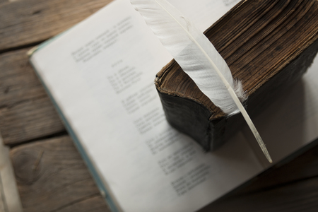 poet: Poet, writer, literature idea. Old book, book of poems and a feather.