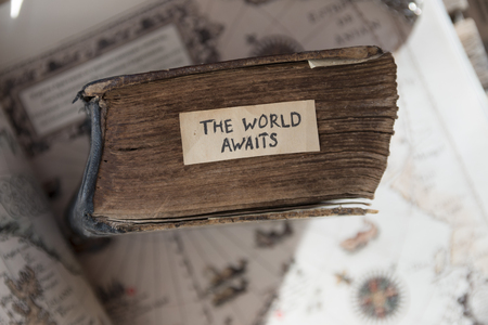 vintage travel: Traveler idea. The World Awaits text, old book and old geographic map