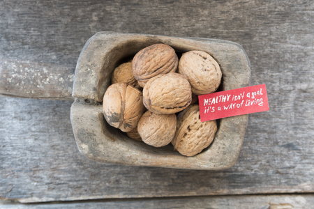 way of living: Healthy isnt a goal. its a way of living - inscription on the label and and walnuts. Healthy lifestyle concept. Stock Photo