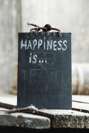 cheerfulness: Happiness is ... Hand lettering on a black plate.