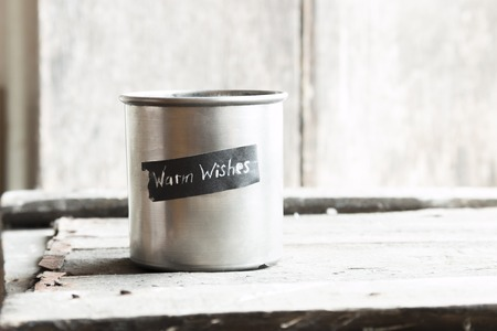 text message: Warm wishes text and cup on a wooden table
