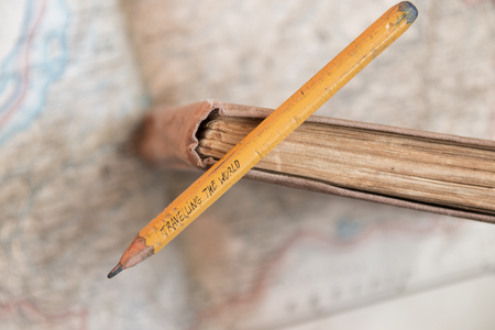 map pencil: Travelling the World inscription on pencil, book and map