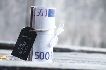 banco dinero: Cómo hacer dinero en línea, la etiqueta con la inscripción y 500 billetes de banco rodado.