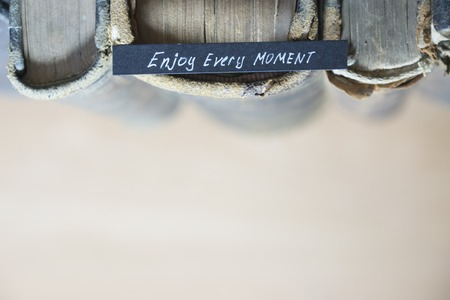 book concept: Enjoy every moment quote, text and old books, toned photo