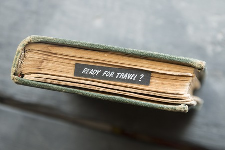 Ready for travel - Text and old book on black table.