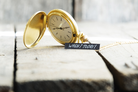 Today idea. Hand writing a note and gold pocket watch Stock Photo
