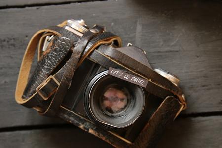 Lässt Reisen, Abenteuer Motivation Konzept gehen. Text und Vintage-Kamera auf einem schwarzen Tisch.